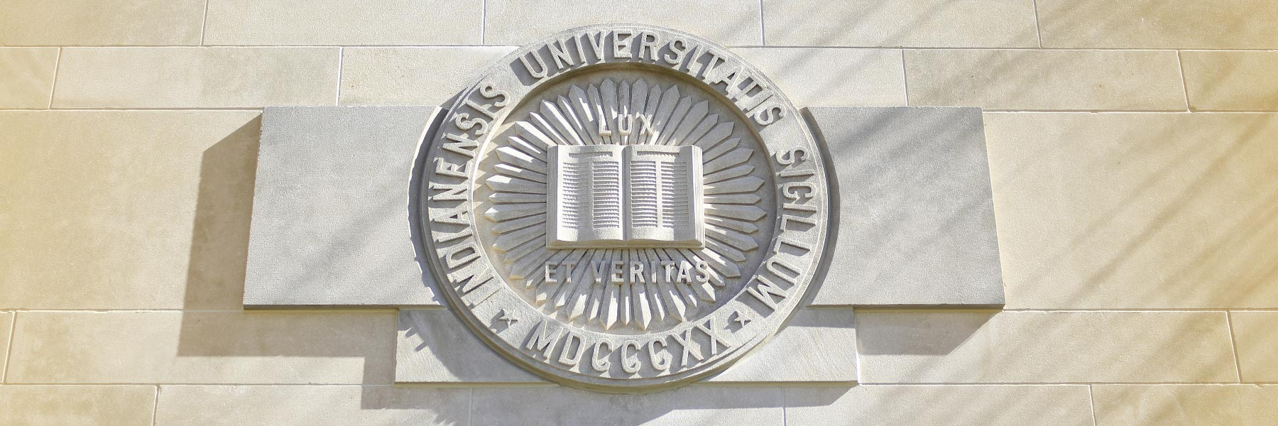 carved IU seal on a limestone building